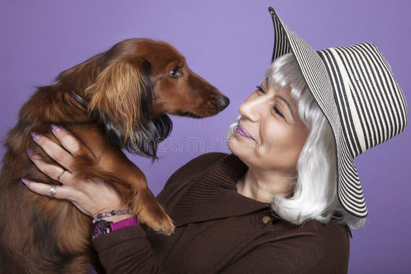 Donna di mezza età che tiene un cane fotografia stock libera da diritti