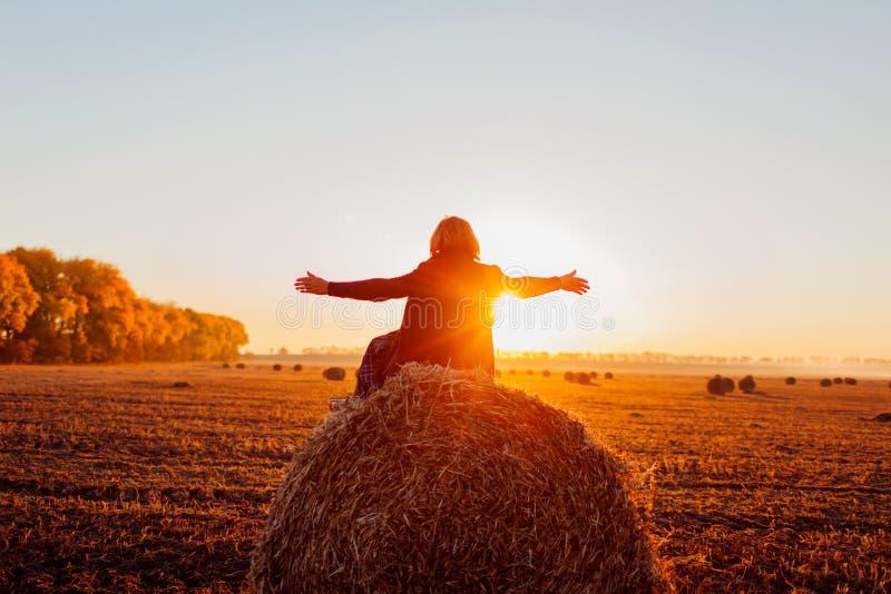 Donna di mezza età felice che si siede sul mucchio di fieno nel campo di autunno e che si sente libero con le armi aperte immagini stock