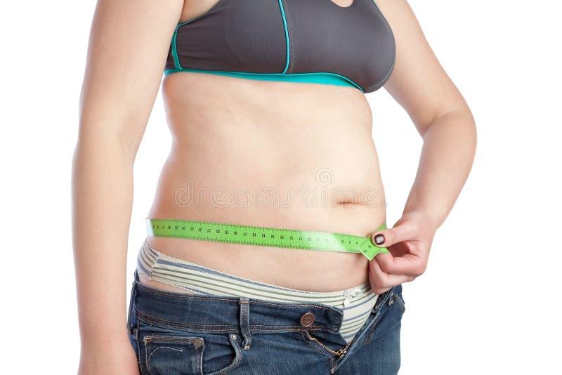 Donna di mezza età grassa che misura la sua vita. fotografie stock