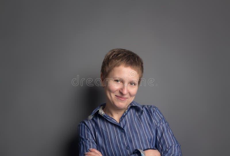 Donna di mezza età sorridente felice in camicia blu immagine stock libera da diritti