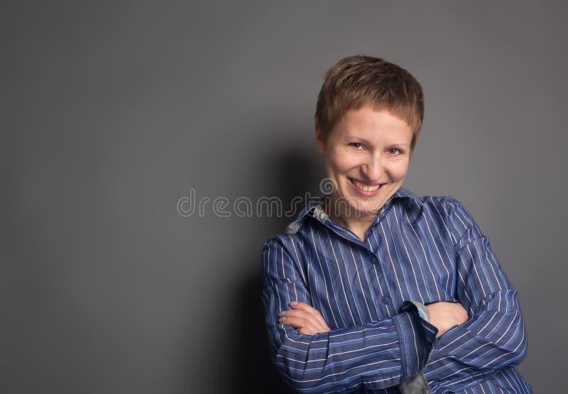 Donna di mezza età sorridente felice in camicia blu fotografie stock