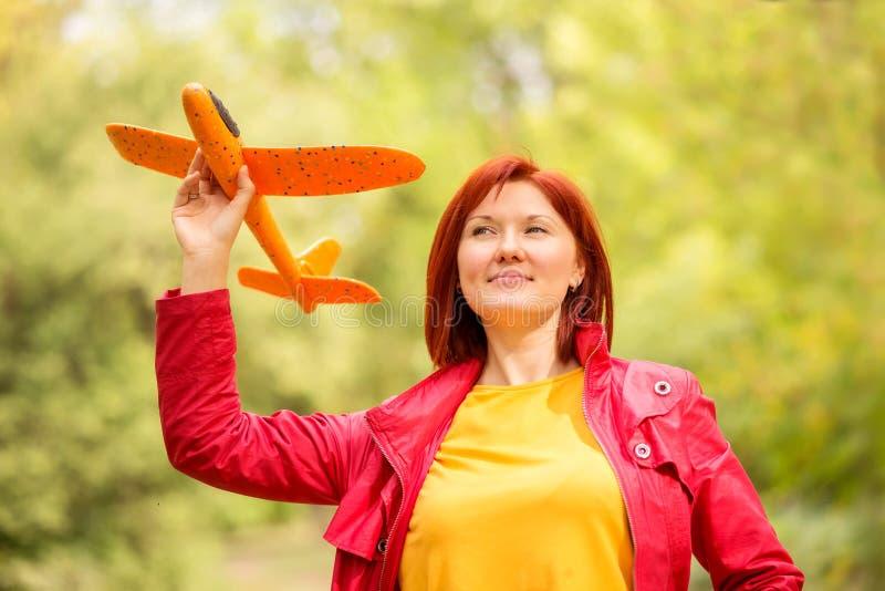 Donna di mezza età sorridente in piedi nel parco autunnale che tiene in mano un aereo giocattolo e guarda in alto nel cielo Conce fotografia stock