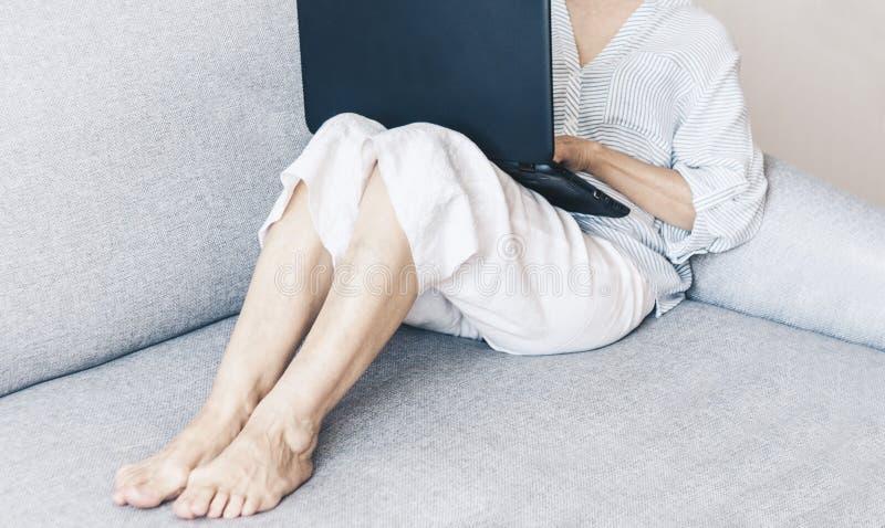 Donna di mezza et? sul funzionamento grigio del sof? sul computer portatile, fuoco molle fotografia stock