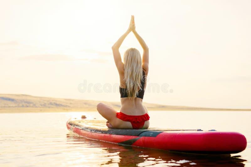 Donna di misura che fa gli esercizi di yoga sul bordo di pagaia nell'acqua al tramonto immagine stock libera da diritti