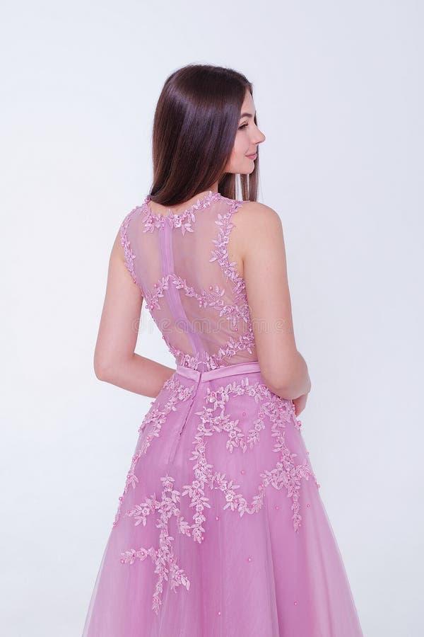 Donna di modello castana di bellezza in vestito da cocktail Trucco di lusso e acconciatura di bello modo Siluetta seducente della immagine stock