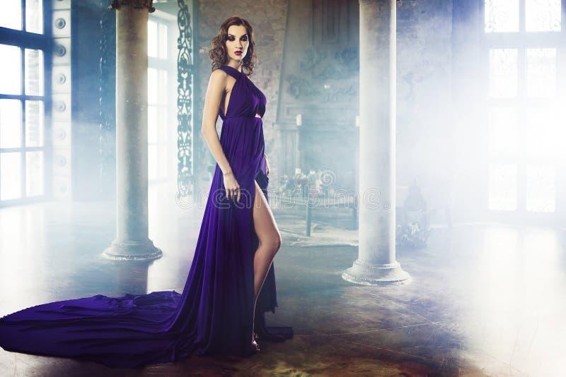 Donna di modello castana di bellezza nell'uguagliare vestito porpora Trucco di lusso e acconciatura di bello modo fotografie stock libere da diritti