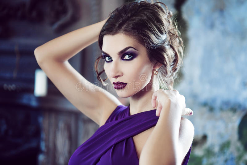 Donna di modello castana di bellezza nell'uguagliare vestito porpora Trucco di lusso e acconciatura di bello modo immagini stock libere da diritti