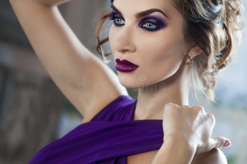 Donna di modello castana di bellezza nell'uguagliare vestito porpora Trucco di lusso e acconciatura di bello modo fotografia stock