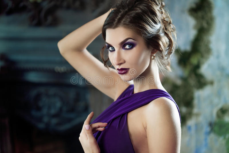 Donna di modello castana di bellezza nell'uguagliare vestito porpora Trucco di lusso e acconciatura di bello modo immagine stock