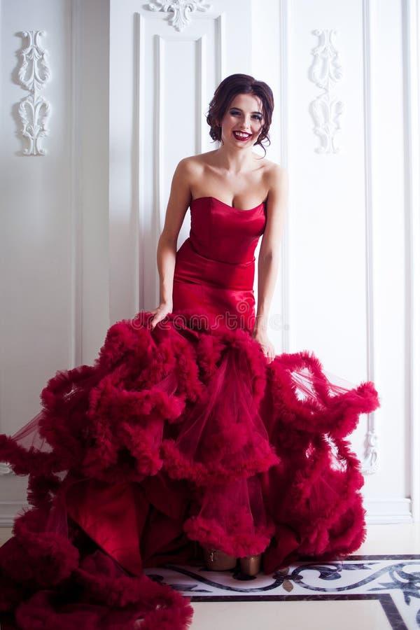 Donna di modello castana di bellezza nell'uguagliare vestito rosso Trucco di lusso e acconciatura di bello modo, integrali fotografia stock libera da diritti