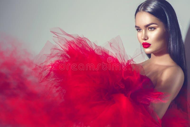 Donna di modello castana splendida in vestito rosso immagine stock