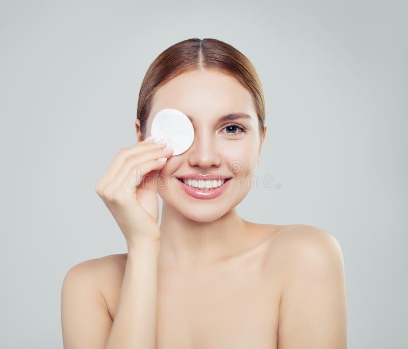 Donna di modello felice con i cuscinetti di cotone Skincare, trattamento facciale, immagine stock
