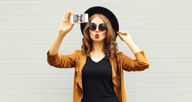 Donna di modo che prende il selfie dell'immagine dallo smartphone in cappello rotondo nero fotografie stock libere da diritti