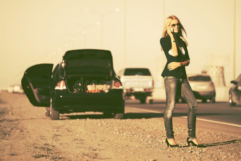 Donna di modo che rivolge al telefono cellulare accanto all'automobile rotta immagini stock