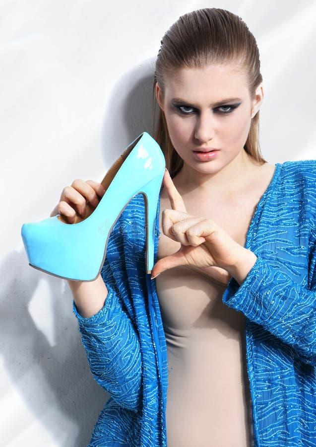 Donna di modo che tiene scarpa elegante fotografia stock