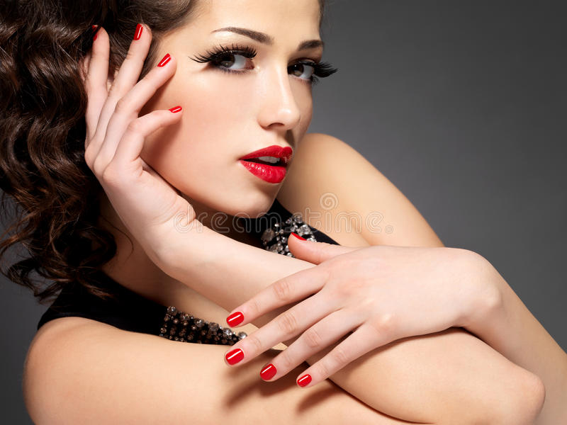 Donna di modo di bellezza con i chiodi rossi ed il trucco immagine stock