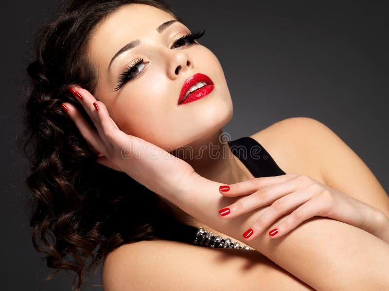 Donna di modo di bellezza con i chiodi rossi ed il trucco fotografia stock