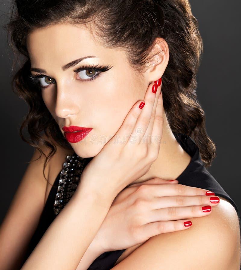 Donna di modo di bellezza con i chiodi rossi ed il trucco fotografia stock libera da diritti