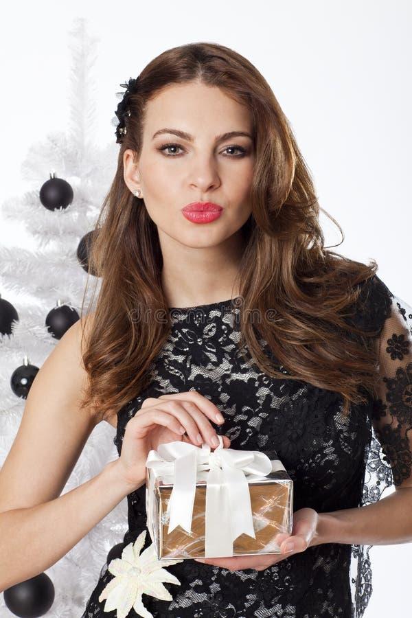 Donna di Natale che decora l'albero di Natale che tiene un contenitore di regalo immagini stock