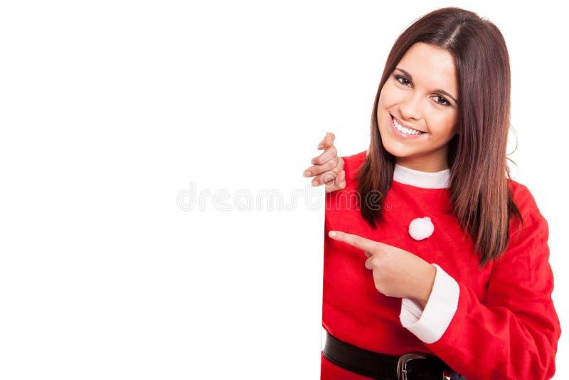 Donna di Natale che indica un'insegna bianca fotografia stock libera da diritti