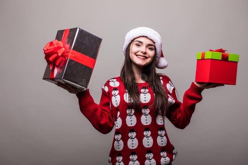 Donna di Natale con i contenitori di regalo La bella ragazza castana che dura nel maglione ed in Santa Hat ha isolato fotografia stock libera da diritti
