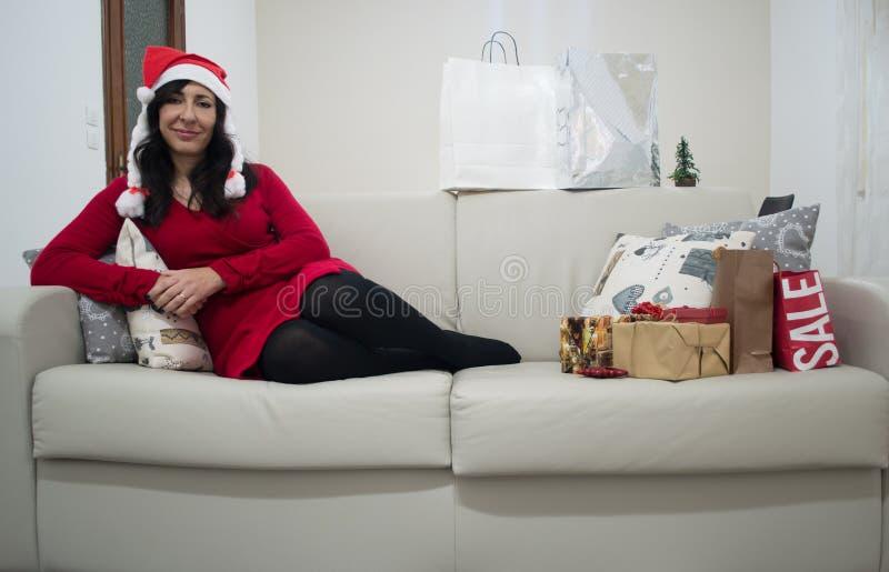 Donna di natale di Santa che si rilassa sul sofà immagine stock