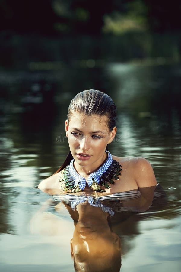Donna di nuoto in collana in stagno immagine stock libera da diritti
