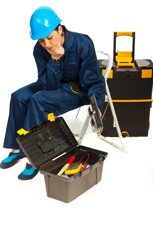 Donna di pensiero dell'operaio con il contenitore di strumenti fotografia stock