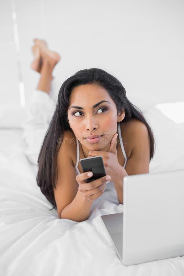 Donna di pensiero naturale che tiene il suo smartphone fotografia stock