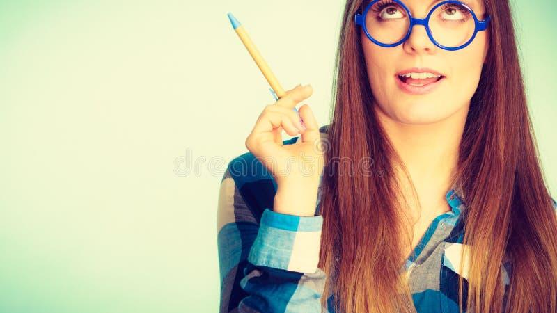 Donna di pensiero nerd nella penna di tenuta di vetro fotografia stock libera da diritti