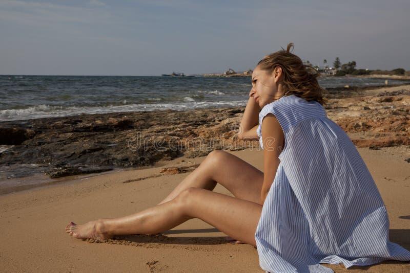 Donna di pensiero sulla spiaggia fotografia stock