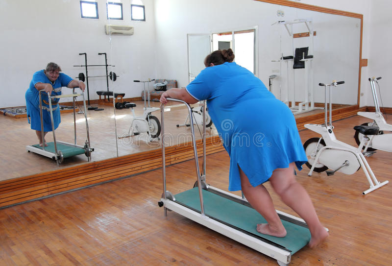 Donna di peso eccessivo che funziona sulla pedana mobile dell'addestratore fotografia stock libera da diritti