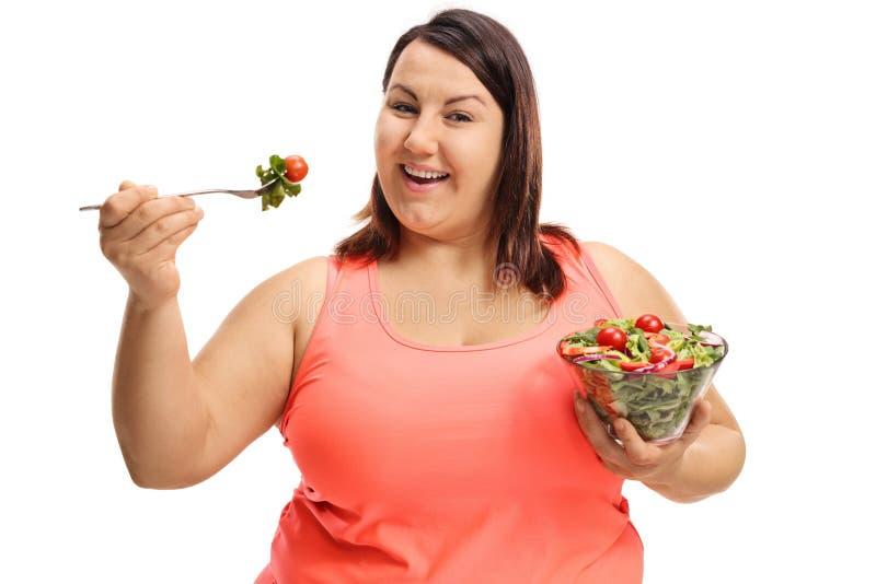 Donna di peso eccessivo che mangia un'insalata fotografia stock