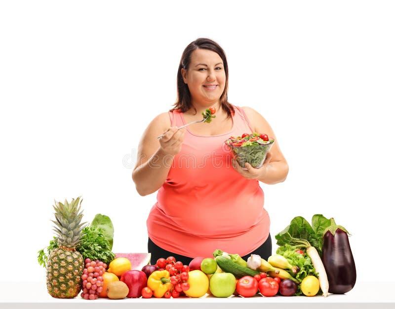 Donna di peso eccessivo che mangia un'insalata dietro una tavola con frutta e la VE fotografia stock
