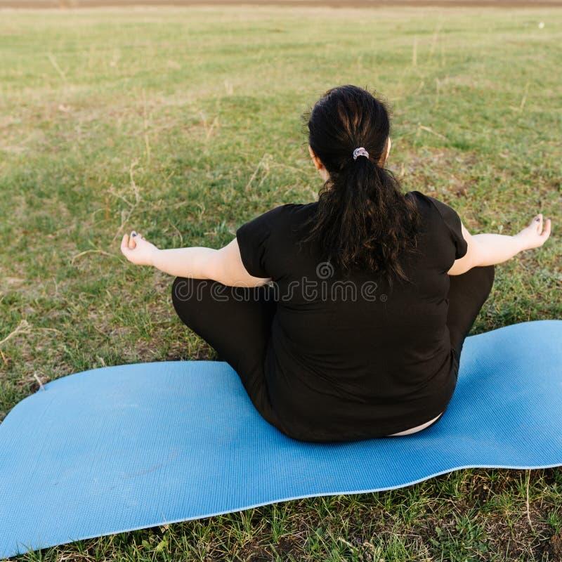 Donna di peso eccessivo che medita alla stuoia di yoga all'aperto immagine stock