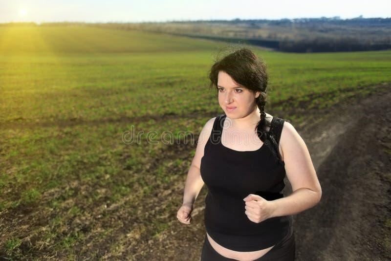 Donna di peso eccessivo che pareggia nella campagna immagine stock