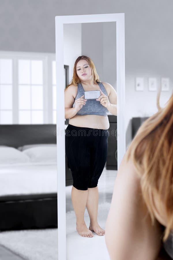 Donna di peso eccessivo che prende immagine nella camera da letto fotografie stock libere da diritti