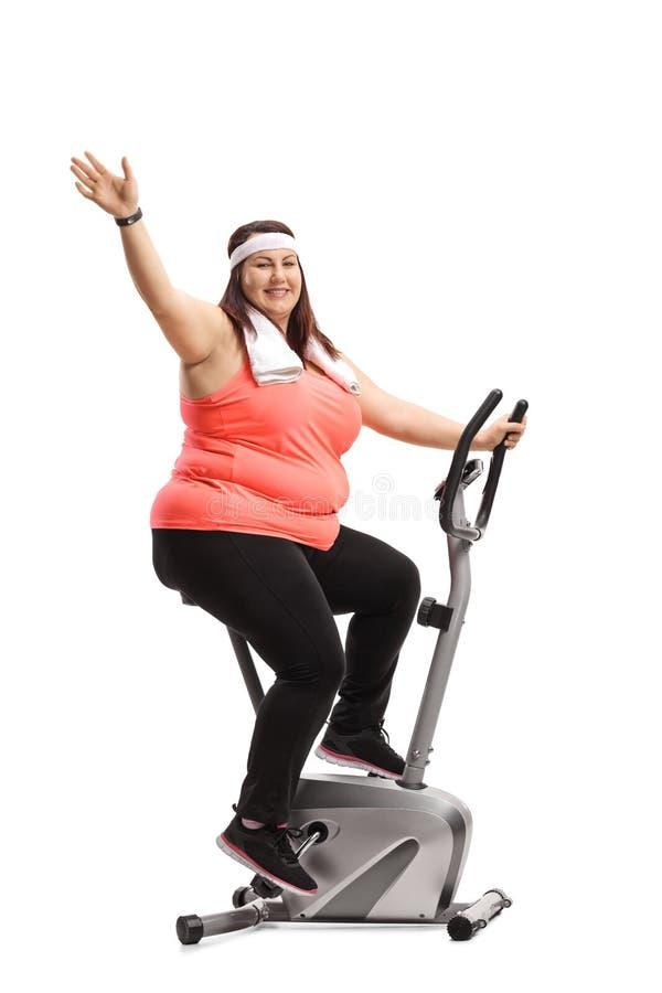 Donna di peso eccessivo che risolve su una bici e su un ondeggiamento di esercizio fotografia stock libera da diritti