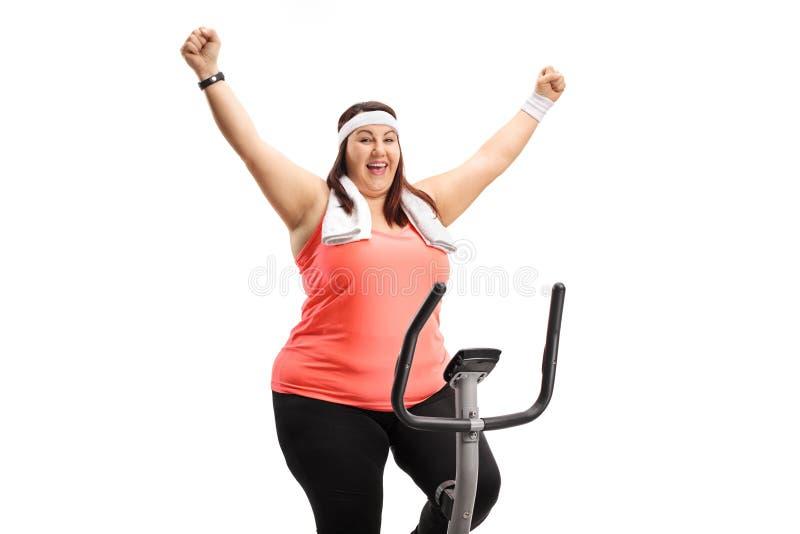 Donna di peso eccessivo che risolve su una bicicletta e su un gesturin di esercizio fotografie stock libere da diritti