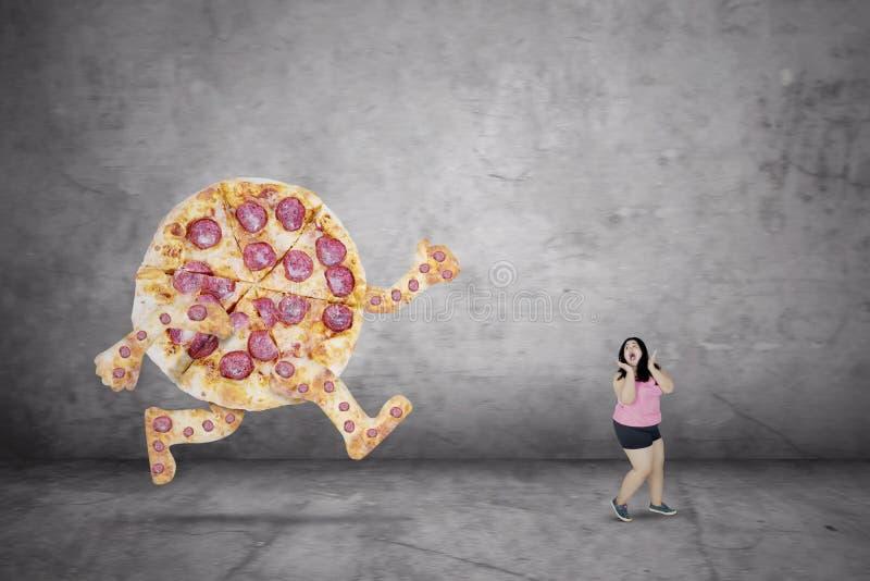 Donna di peso eccessivo che sfugge da una pizza immagini stock libere da diritti
