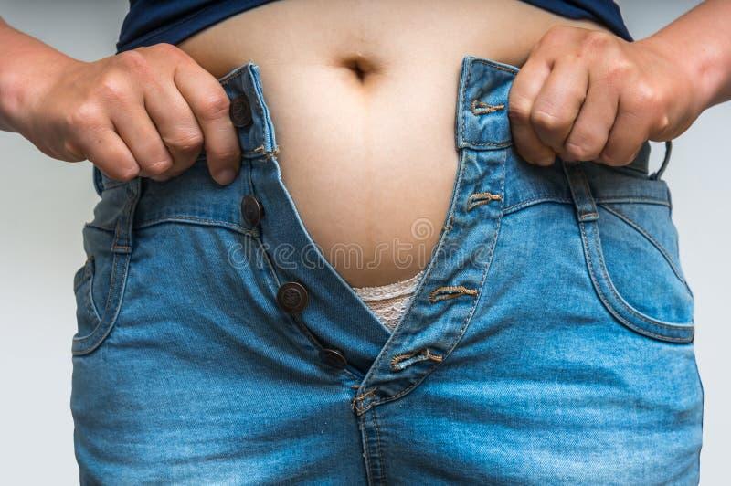 Donna di peso eccessivo che si veste i jeans d'uso immagine stock
