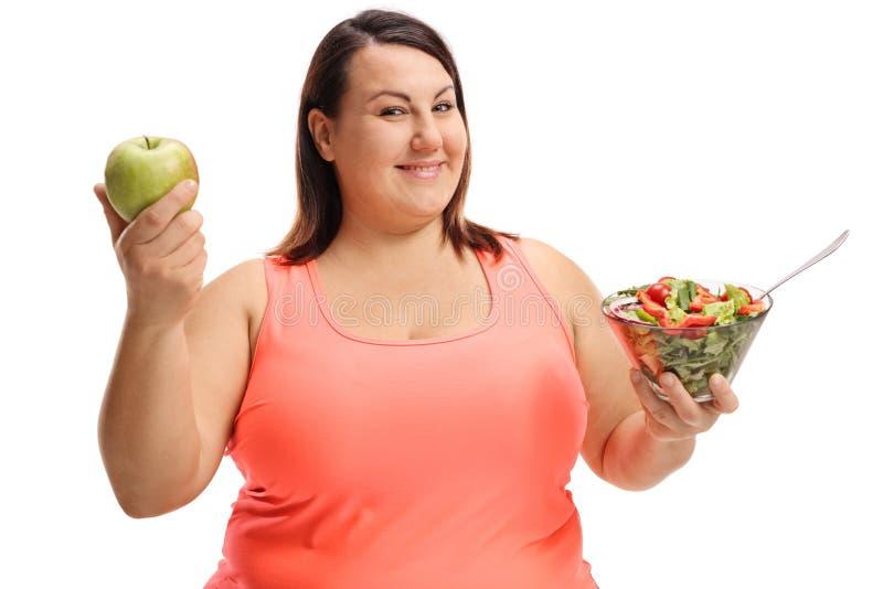 Donna di peso eccessivo che tiene una mela e un'insalata fotografia stock