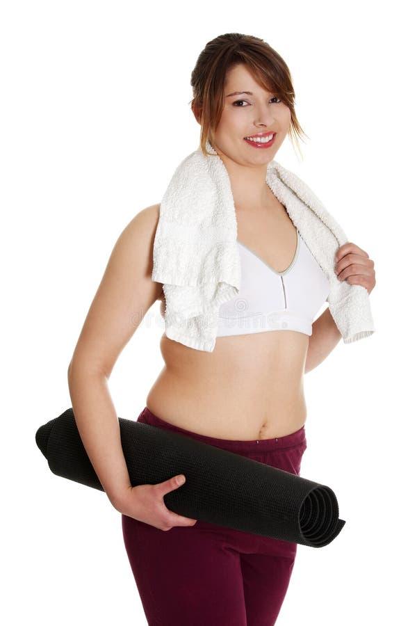 Donna di peso eccessivo con il tovagliolo e la stuoia di yoga fotografia stock libera da diritti