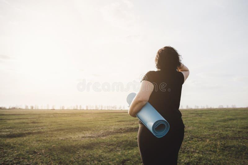 Donna di peso eccessivo con la stuoia di yoga all'allenamento all'aperto fotografie stock