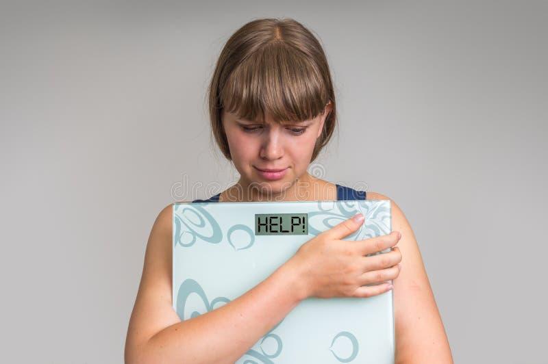 Donna di peso eccessivo frustrata che tiene le scale digitali con AIUTO! immagini stock