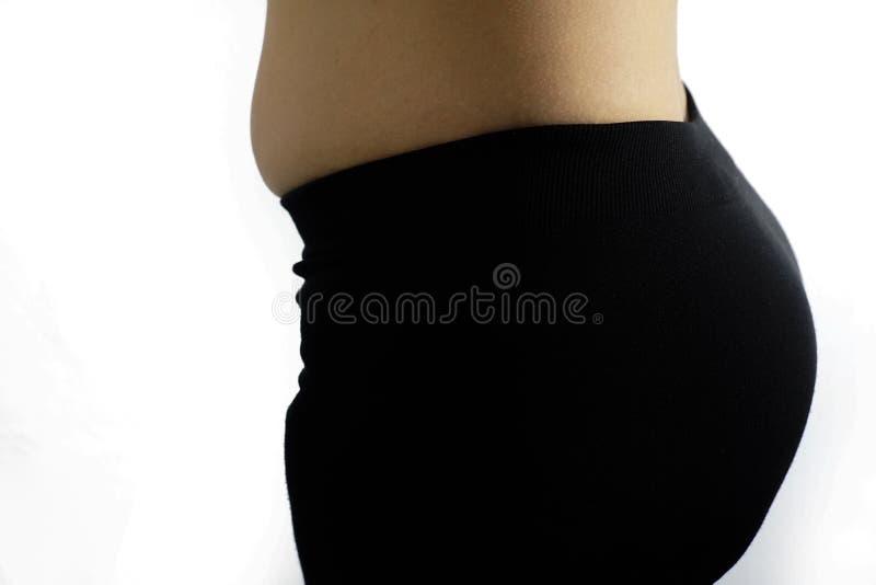 Donna di peso eccessivo grassa che pizzica la sua pancia grassa isolata su fondo bianco, donna obesa, donne con la pancia grassa fotografia stock
