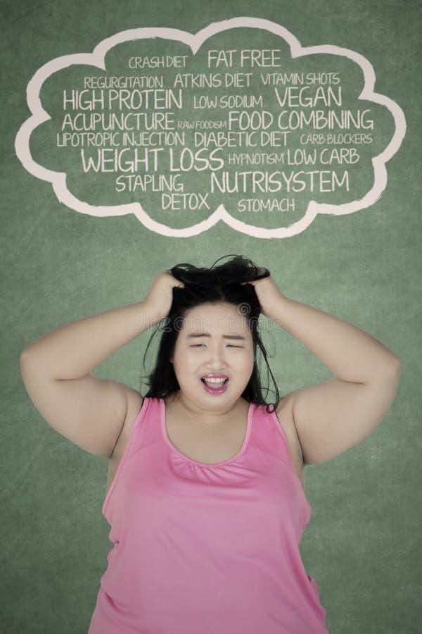 Donna di peso eccessivo sollecitata che pensa i suoi problemi fotografia stock libera da diritti