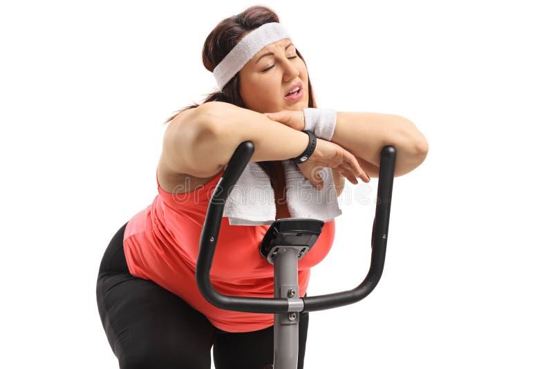 Donna di peso eccessivo stanca che dorme su una bici di esercizio fotografia stock