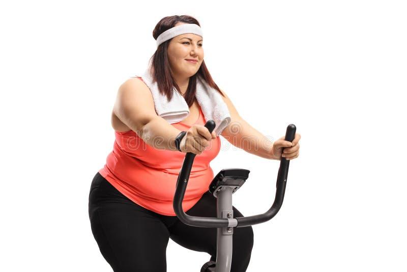 Donna di peso eccessivo su una bici di esercizio fotografia stock libera da diritti
