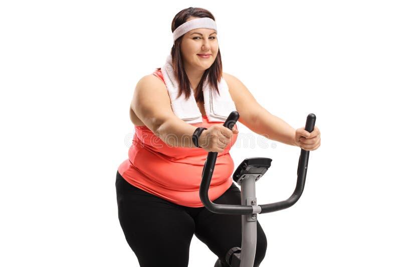 Donna di peso eccessivo su una bici di esercizio fotografia stock
